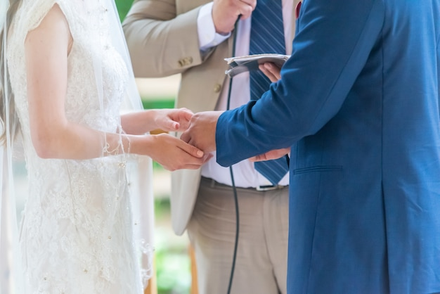Bride in a luxurious white dress and a groom in a blue suit during wedding ceremony with the priest
