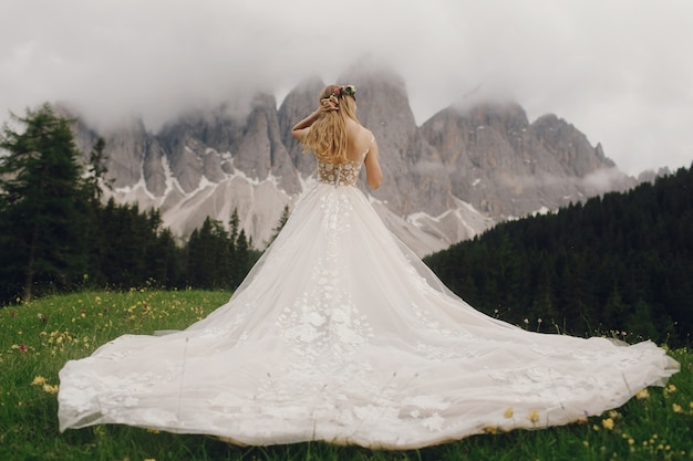 Bride in a luxury dress stands before beautiful mountain landscape