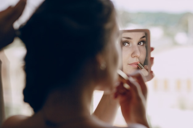 Bride making  up in a small mirror