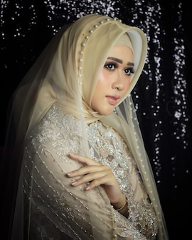 A bride model by wearing muslim clothing and minimalist makeup