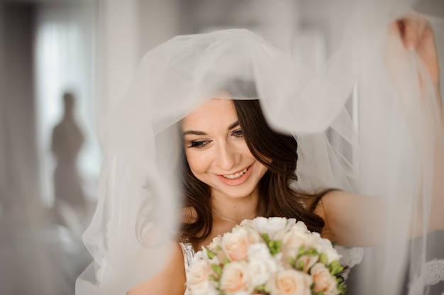 Bride morning preparation. attractive and smiling bride in a white veil with a wedding bouquet