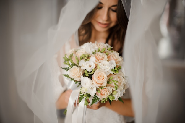 Bride morning preparation. portrait of a lovely bride in a white veil with a wedding bouquet