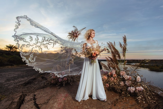 The bride near the wedding decoration at a ceremony on a cliff of rock near the water at sunset. veil flying from the wind