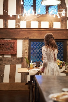 Bride near the wedding table with white decorations, old english house