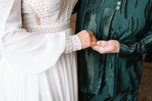Невеста в день свадьбы, взявшись за руки матери