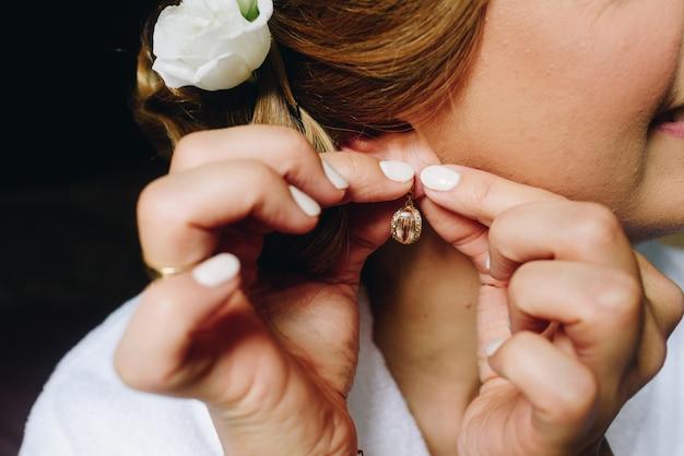 Невеста или подружка невесты надевают серьги готовится
