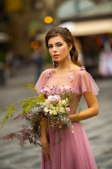 A bride in a pink dress with a bouquet stands in the center of the old city of florence in italy.