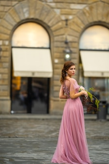 A bride in a pink dress with a bouquet stands in the center of the old city of florence in italy