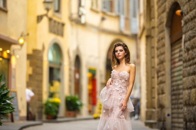 A bride in a pink wedding dress walks in florence, italy.
