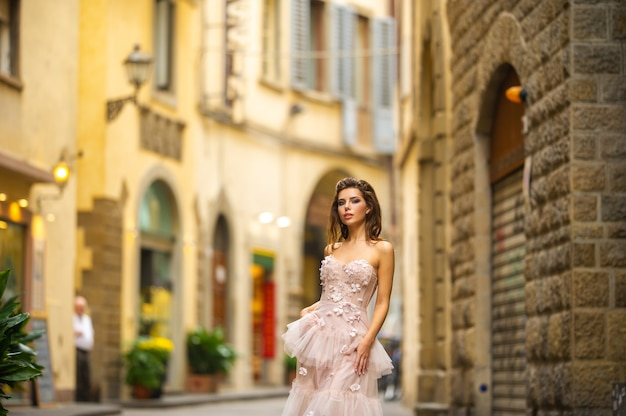 Bride in a pink wedding dress walks in florence, italy.