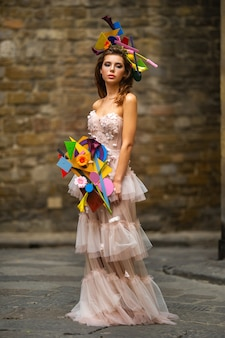 A bride in a pink wedding dress with an unusual bouquet and decoration in gorova in florence, italy.