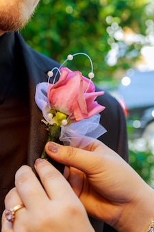 Bride pins a boutonniere to groom's blue jacket
