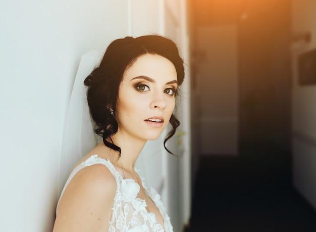 カメラの廊下でポーズをとる花嫁
