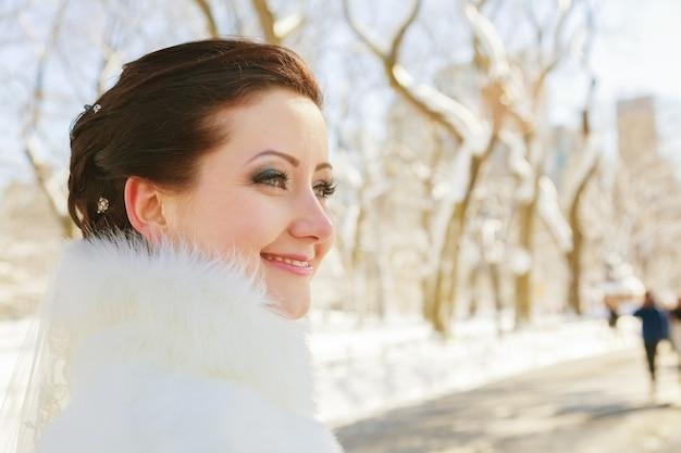 毛皮のコートで冬の森でポーズをとる花嫁。雪に覆われた公園での結婚式のフォトセッション。