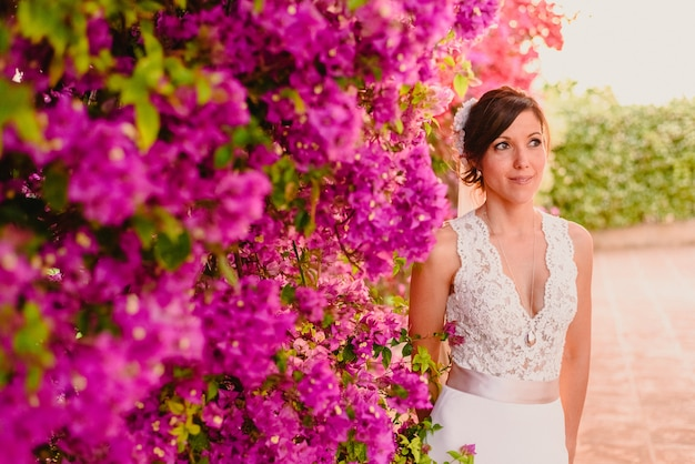 Bride posing on wedding day next to flowers