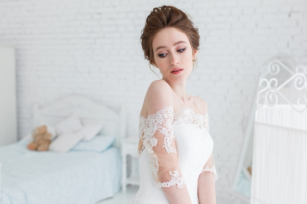 Bride posing in wedding dress in the studio on a background of a brick wall and white bed