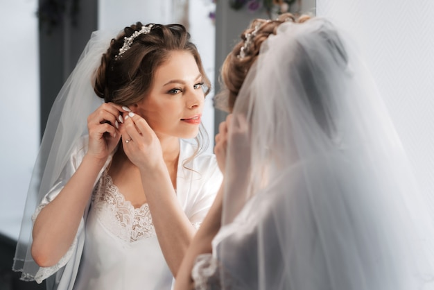 Bride puts on earrings in her ears while looking at herself in the mirror