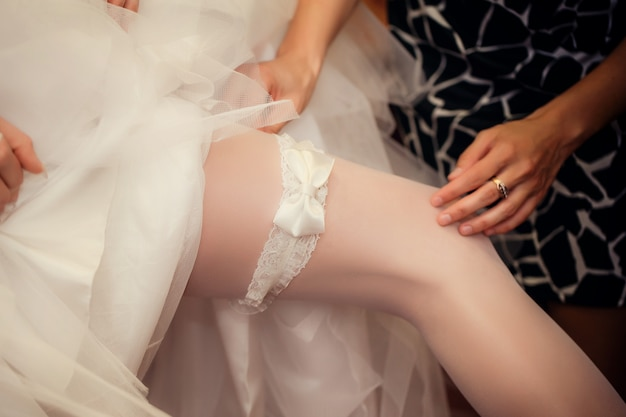 Bride puts on a garter on a foot