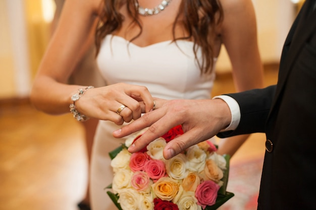 Bride puts ring on groom's finger over bright wedding bouquet