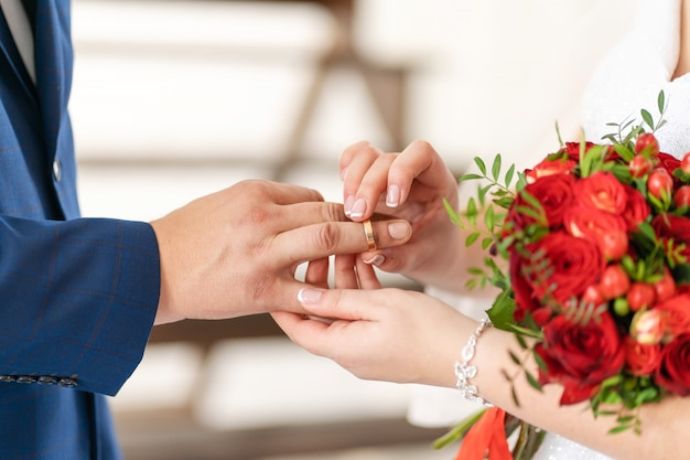 The bride puts a wedding ring on the finger of the groom. wedding details.