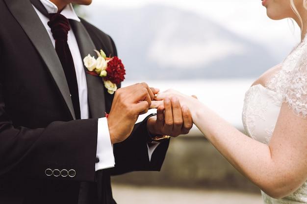 Bride puts wedding ring on groom's finger