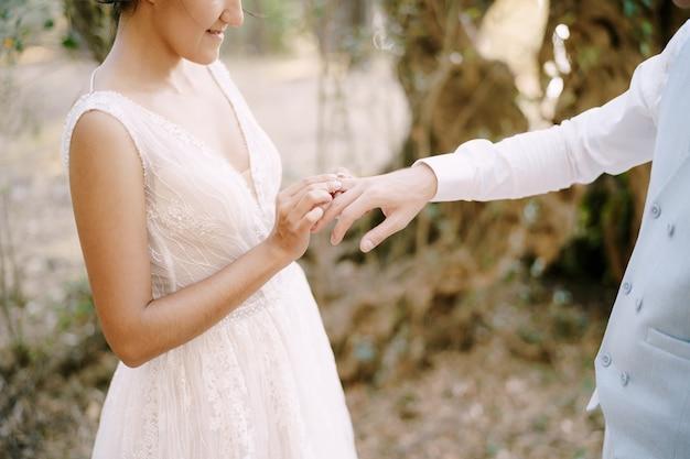 신부는 올리브 과수원에 있는 나무들 사이에서 신랑의 손가락에 결혼 반지를 끼웁니다. 고품질 사진