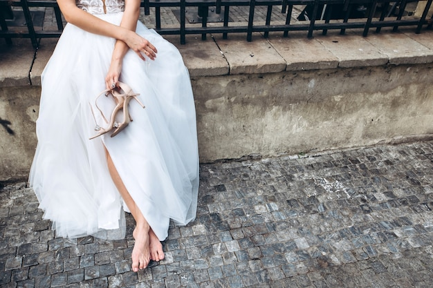 The bride puts on wedding shoes.