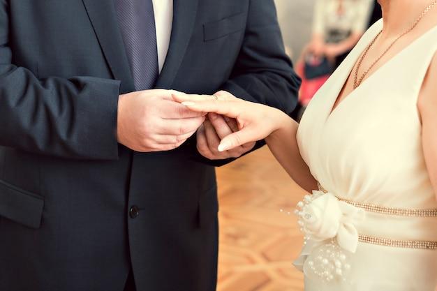 結婚式中に新郎の指に指輪を置く花嫁