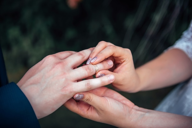 Bride putting gold wedding ring on groom's finger during wedding ceremony, close up.