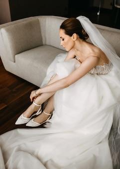 Невеста надевает туфли, сидя на диване.