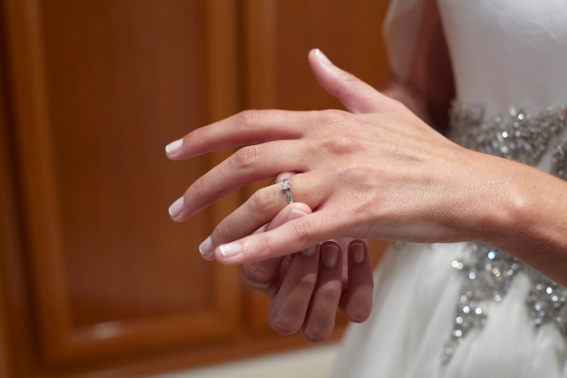 Bride putting on her wedding ring