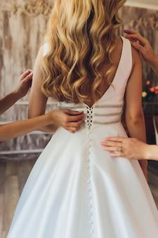 Bride putting on her white wedding dress. wedding celebration concept.