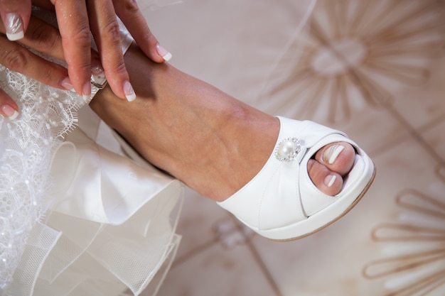 Bride putting on her white wedding shoes