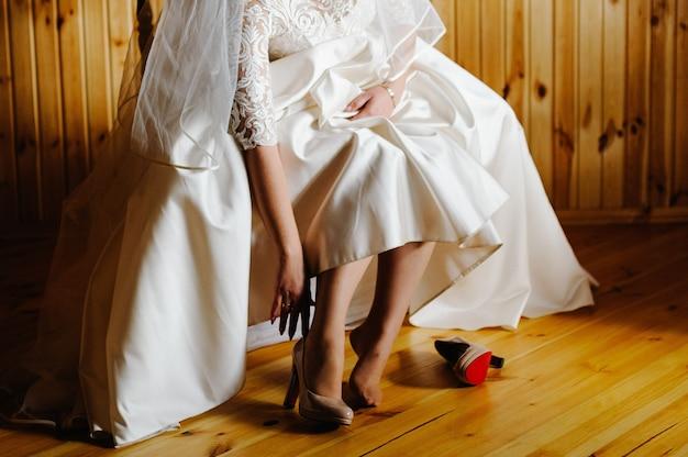 スタイリッシュでクラシックな漆塗りのベージュの靴を履く花嫁。
