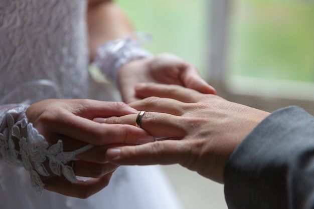 Bride putting the wedding ring on groom finger close up.