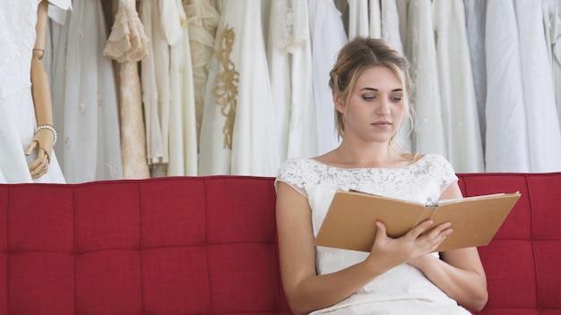 Bride reading book or catalogue in wedding studio.