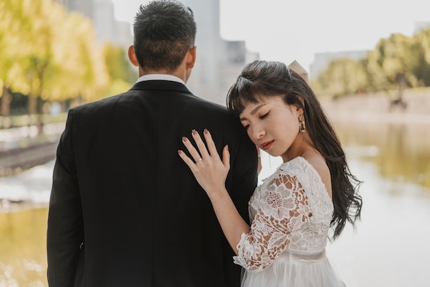 Sposa che riposa la sua testa sulla spalla dello sposo