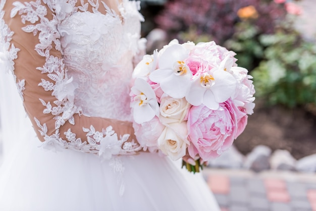 Bride in rich dress holds pink wedding bouquet of orchids and peonies