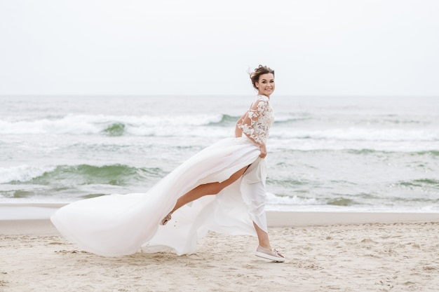Bride runs along the sea beach on a cloudy day