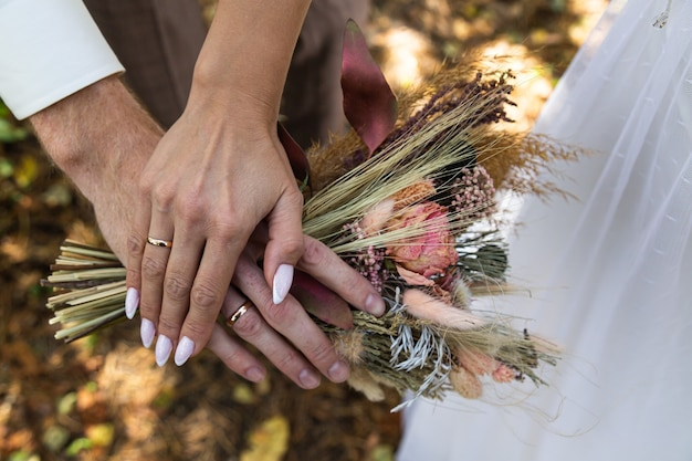 The bride's bouquet of dried flowers in the hands of the newlyweds.