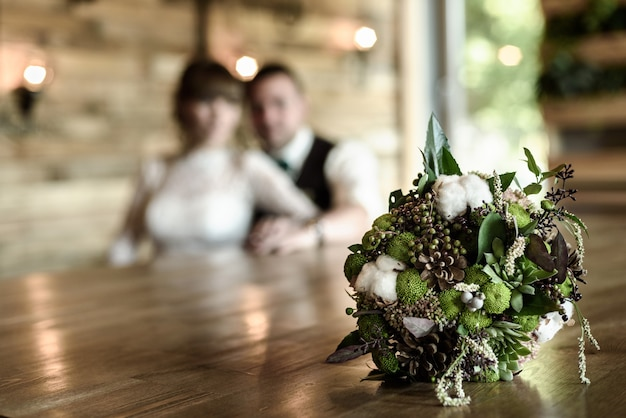 The bride's bouquet from cones and cotton close up in natural light on a wooden table