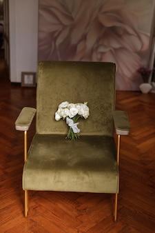Букет невесты на зеленом винтажном кресле