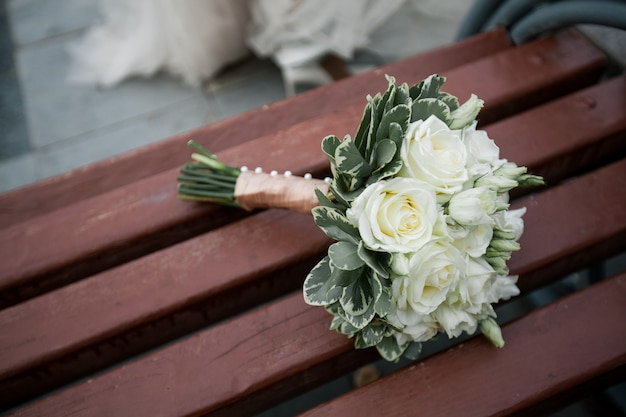 Bride's bouquet of white roses on a wooden bench.