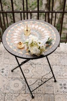 Букет невесты с бокалом шампанского и духами на круглом столе на балконе.