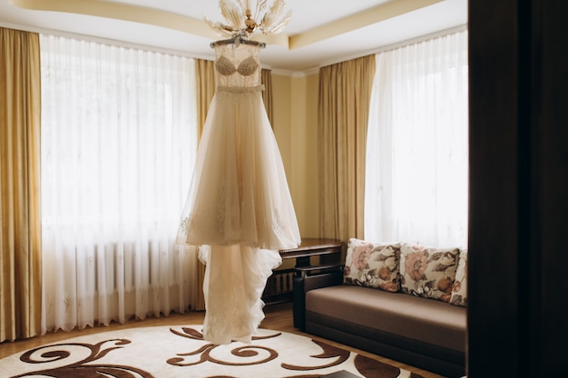 Bride's dress hangs on a chandelier