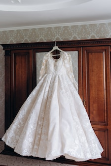 Bride's dress hangs on a wardrobe