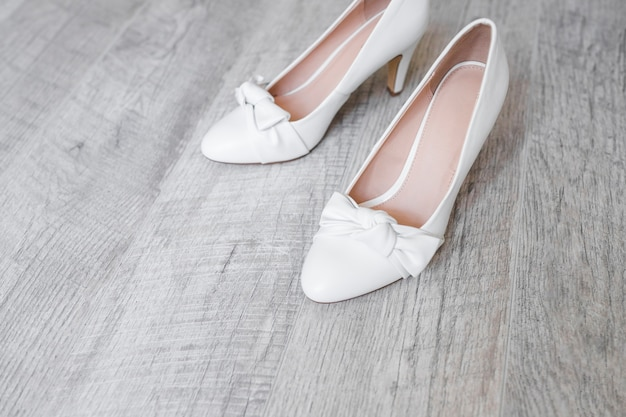Bride's dress shoes on wooden textured backdrop