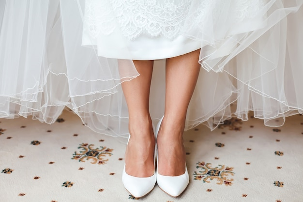 Bride's feet in shoes under wedding dress