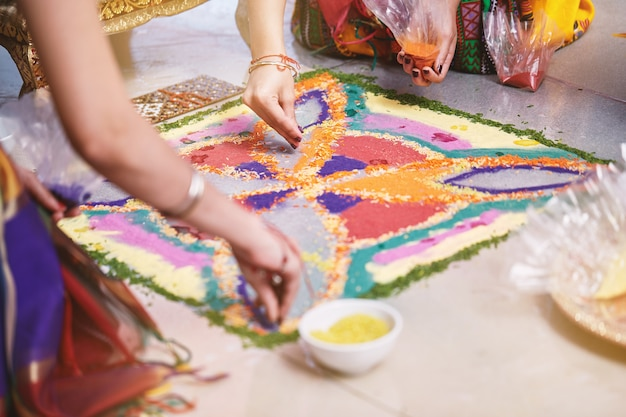Bride's friend helps coloring the traditional rice art
