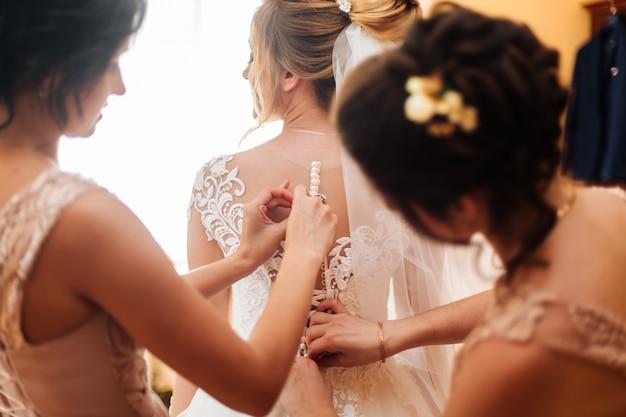 花嫁のガールフレンドは彼女の結婚式の日に花嫁を準備します。花嫁のガールフレンドは、式典の前に花嫁のウェディングドレスを確保するのに役立ちます